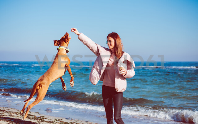 Mid adult woman on beach playing with her dog, Odessa, Odeska Oblast, Ukraine - ISF20209 - Rehulian Yevhen/Westend61