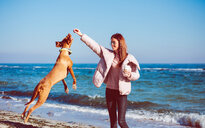 Mid adult woman on beach playing with her dog, Odessa, Odeska Oblast, Ukraine - ISF20209