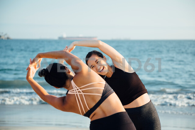 Friends doing exercises on beach - ISF20218