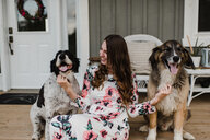 Woman and her two dogs sitting on porch - ISF20248