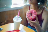 Young woman holding doughnut in cafe - ISF20266