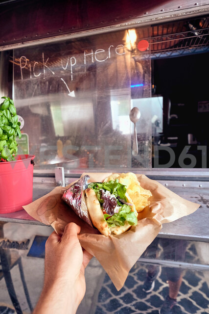 Salad wrap being collected from window of food truck - ISF20299