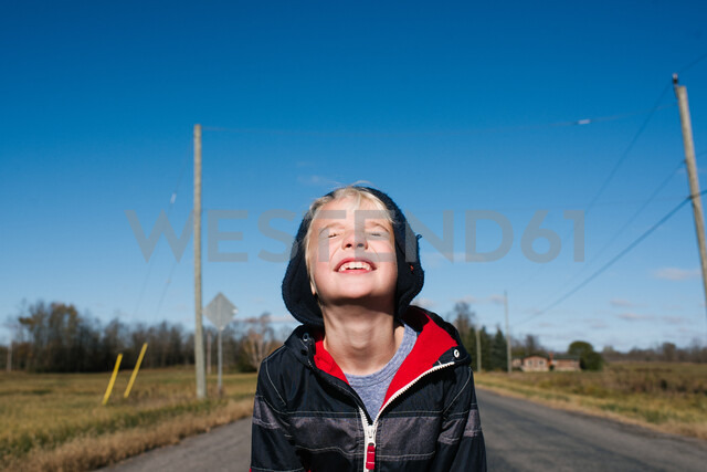 Boy squinting against clear blue sky - ISF20311