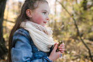 Little girl holding frog in forest - ISF20317