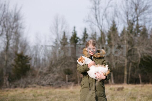 Girl cuddling cat in field - ISF20320