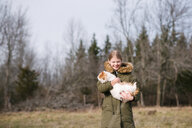 Girl cuddling cat in field - ISF20320