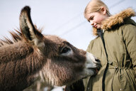 Donkey licking girl's parka - ISF20323