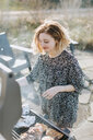 Young woman cooking on barbecue, Menemsha, Martha's Vineyard, Massachusetts, USA - ISF20338