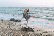 Young woman balancing on beach rock, Menemsha, Martha's Vineyard, Massachusetts, USA - ISF20344