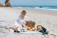 Young woman picnicking on beach, Menemsha, Martha's Vineyard, Massachusetts, USA - ISF20350