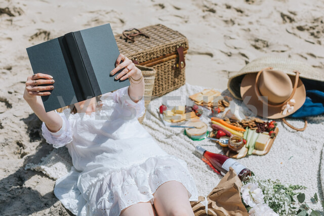 Young woman on picnic blanket at beach reading book, Menemsha, Martha's Vineyard, Massachusetts, USA - ISF20353