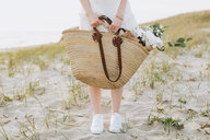 Young woman carrying shoulder bag with flowers on coastal dunes,  waist down, Menemsha, Martha's Vineyard, Massachusetts, USA - ISF20362