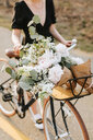 Young woman pushing bicycle with bunch of flowers on rural road, neck down, Menemsha, Martha's Vineyard, Massachusetts, USA - ISF20368