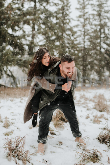 Couple playing piggyback in snowy landscape, Georgetown, Canada - ISF20371