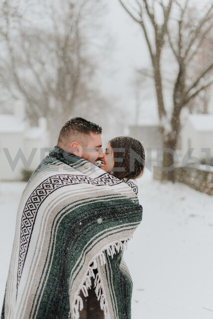 Couple wrapped in blanket kissing in snowy landscape, Georgetown, Canada - ISF20401 - Sara Monika/Westend61
