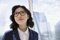 Pensive businesswoman at urban office window - HEROF05452