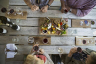 Overhead view couples wine tasting and enjoying charcuterie board at winery tasting room - HEROF05518