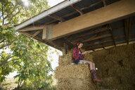 Girl with headphones listening to music on hay bale in barn - HEROF05521