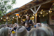 Man leading toast at outdoor dinner party under string lights - HEROF05557