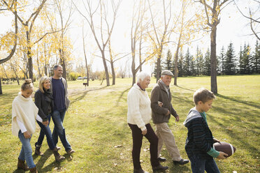Multi-generation family walking with football in sunny autumn park - HEROF05566