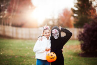 Siblings in halloween costume posing in park - ISF20464