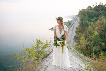 Bride with bouquet on clifftop by coast, Scarborough Bluffs, Toronto, Canada - ISF20476