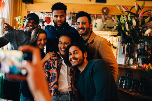 Young woman photographing cheerful multi-ethnic friends standing at restaurant during brunch - MASF10861