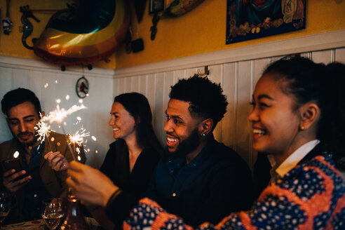Happy multi-ethnic male and female friends holding burning sparklers in restaurant during dinner party - MASF10876