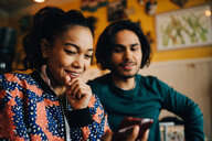Smiling young man and woman sharing smart phone while sitting at restaurant during brunch - MASF10888