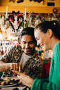 Smiling young man pointing at smart phone to woman sitting in restaurant during brunch party - MASF10894
