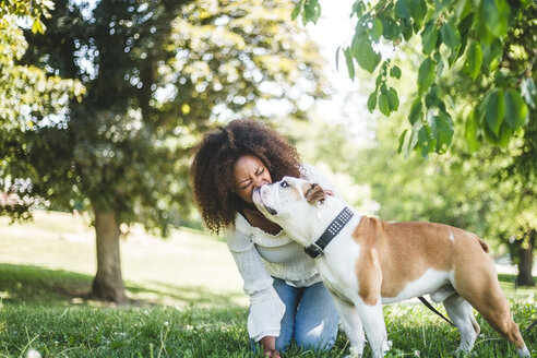 Happy mid adult woman with affectionate bulldog at park - MASF10927