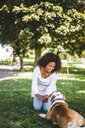 Smiling mid adult woman holding stick while playing with dog at park - MASF10930