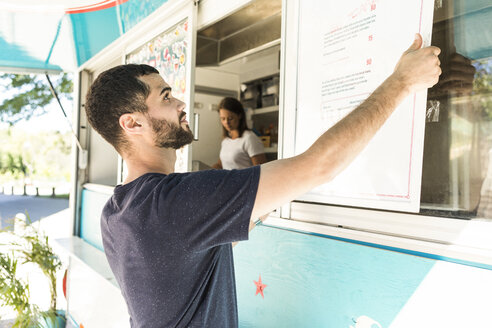 Confident young male salesman positioning menu placard on food truck - MASF10978