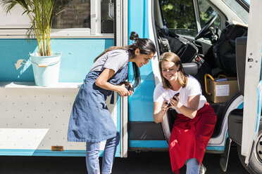 Happy young multi-ethnic female owners sharing smart phone against food truck - MASF10981