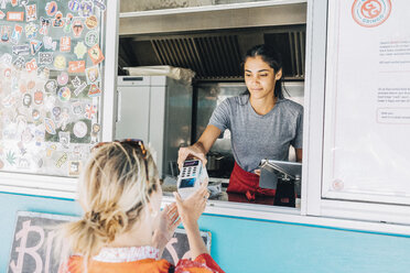 Young female owner standing giving credit card reader to blond customer at concession stand - MASF10990