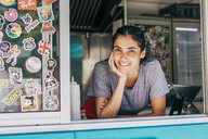 Portrait of smiling young female saleswoman leaning on food truck window - MASF10993