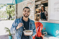 Portrait of smiling young man eating fresh Tex-Mex in bowl against food truck - MASF10996