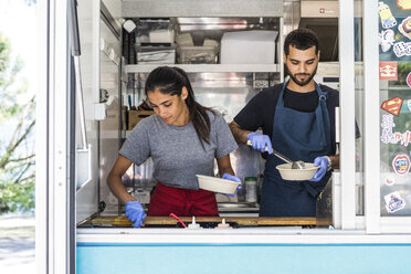 Confident young multi-ethnic male and female colleagues working in food truck - MASF11002
