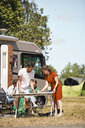 Parents arranging table while siblings sitting against van at trailer park during summer - MASF11032