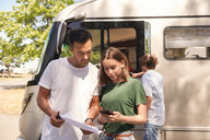 Daughter with smart phone assisting father in reading map while standing against camper van - MASF11035