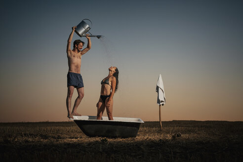 Man with watering can showering woman in bathtub in rural field - FSIF03731