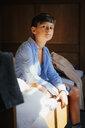 Portrait confident boy sitting on bed - FSIF03734