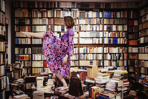 Exuberant woman dancing on book stacks in library - FSIF03746