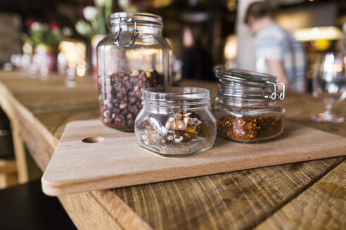 Close-up of nuts and chili flakes in jar on restaurant table - ASTF02216