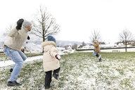 Wickede, NRW, Deutschland. Ein Vater spielt  mit den Kindern mit Schnee im Winter im Freien - KMKF00681