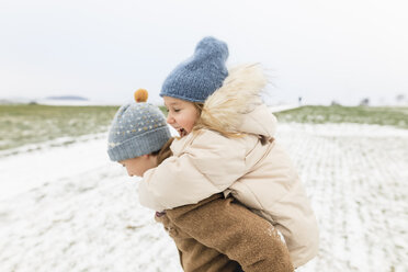 Boy carrying happy sister piggyback in winter landscape - KMKF00684