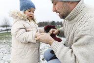 Father helping daughter putting on gloves in winter - KMKF00687