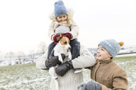 Happy father with two children and dog in winter landscape - KMKF00693