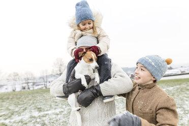 Wickede, NRW, Deutschland. Ein Vater spielt  mit den Kindern und einem Jack Russell Terrier Hund  mit Schnee im Winter im Freien - KMKF00693