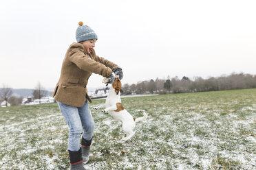 Wickede, NRW, Deutschland. Ein Teenager spielt mit dem Jack Russell Terrier Hund  beim ersten Schnee im Winter - KMKF00696